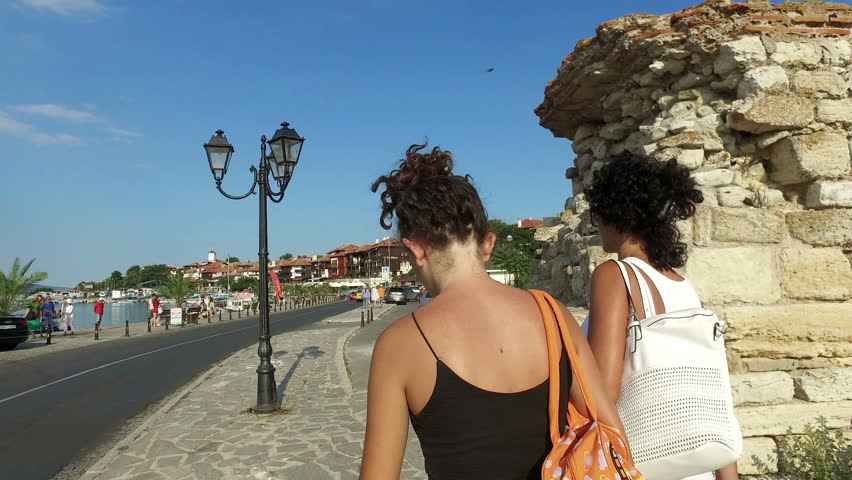 Tourists, mother and daughter walk near ruined tower and stone walls around the old Nessebar town, Bulgaria