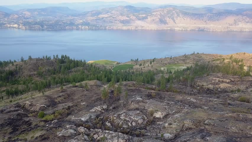 Okanagan Lake and valley. British Columbia finest views. Hills in morning light, distant vineyards. Some smoke from wildfires. filmed in aerial drone view from above. different angles available