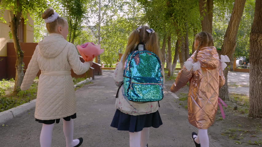 Three girls with flower bouquets walking to school, back view