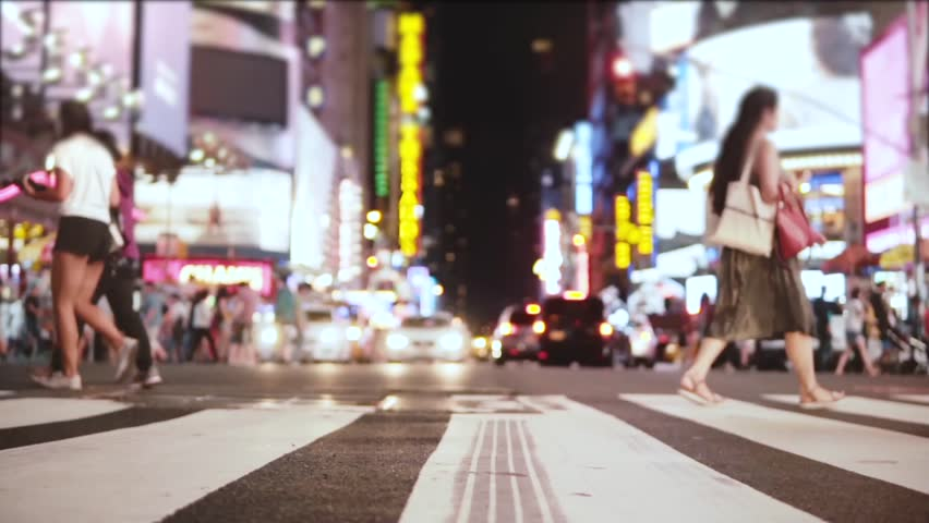 Amazing low angle slow motion shot of crowd walking across the street with many ads at night on Times Square, New York. #1016040706