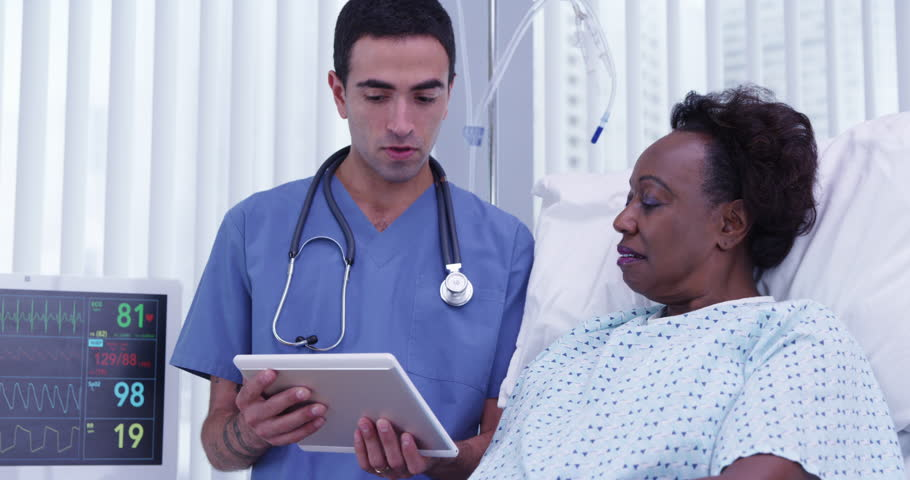 Senior female black patient lying in hospital bed listening to doctor talk about her procedure. Portrait of young male doctor using electronic notebook tablet to show female patients health condition