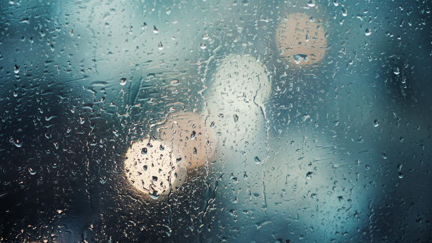 Close up view of water drops falling on glass. Rain running down on window. Rainy season, autumn. Raindrops trickle down, grey sky. Great for special effects and motion graphics