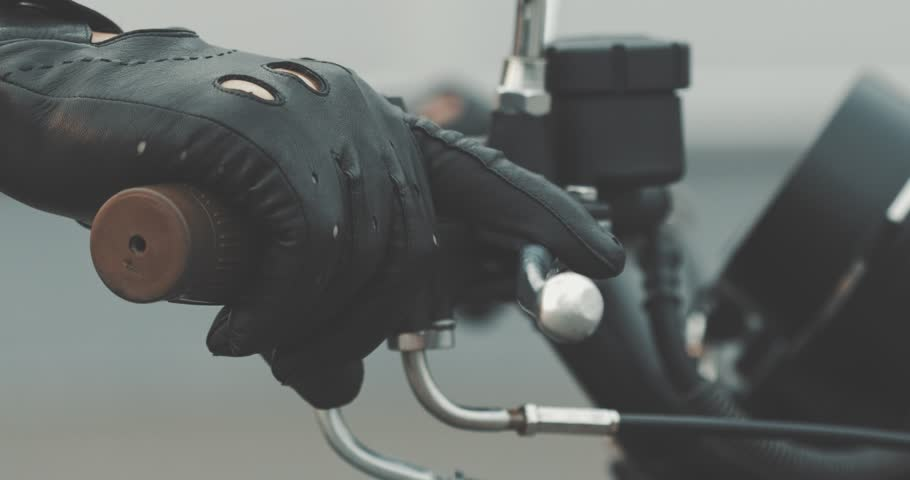 Motorbike handle grips. Close up the hand of the motorcyclist holds the trottle and pushes the brake lever. The biker inserts the key into the ignition lock and turns the bike.