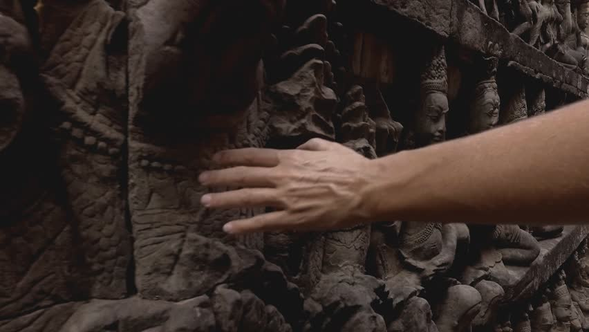 Female's hand touching ancient statue in temple in Asia, statues and carvings on walls - Video Hd format 1080p People travel destinations Asia concept
