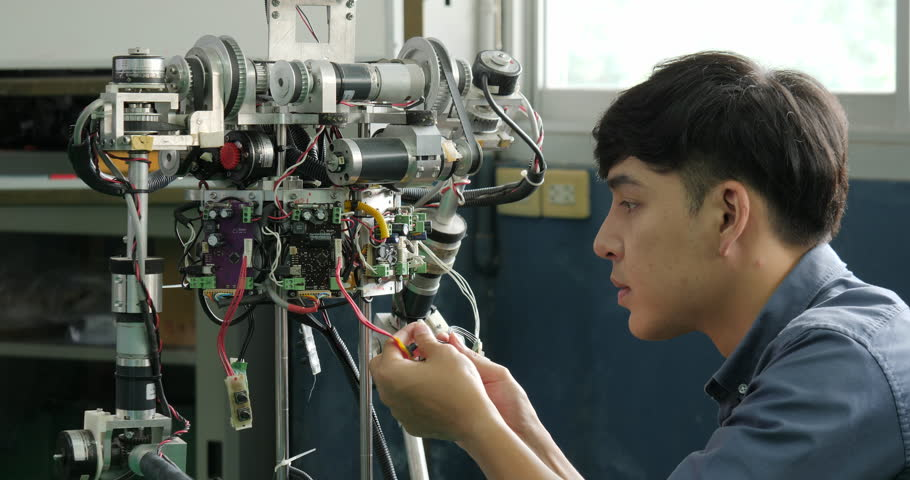 Asian young electronics engineer building, fixing robotics in laboratory. People with technology or innovation concept.