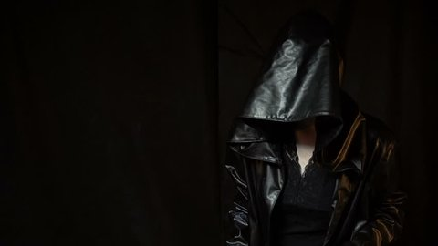 Woman in black hood with anaconda