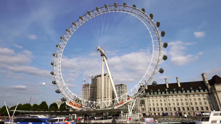 Low angle moving shot of London Eye ferris wheel over Thames River in London Great Britain  | Shutterstock HD Video #1016089423