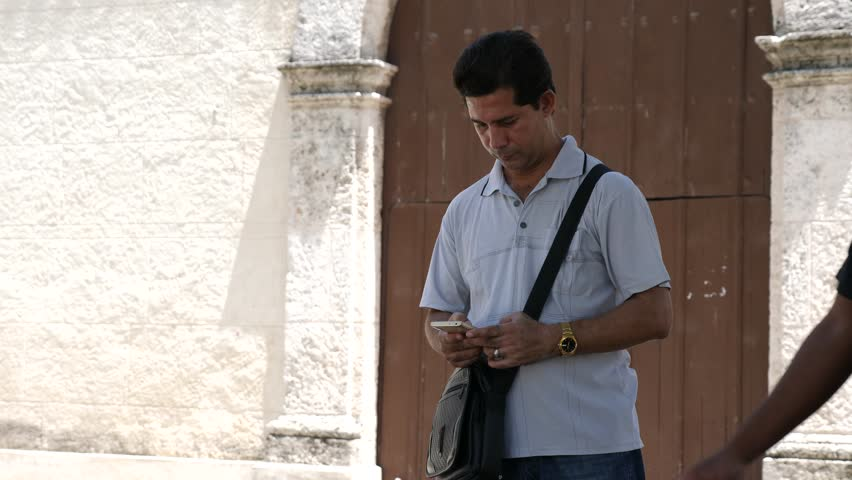 Havana / Cuba - August 26 2018: Local Cubans and Tourists use Internet Access Wireless Technology in a Public Wifi Network plaza.  | Shutterstock HD Video #1016092948