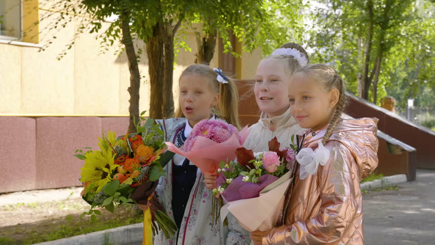 Three school girls with flowers posing for camera. Back to school concept