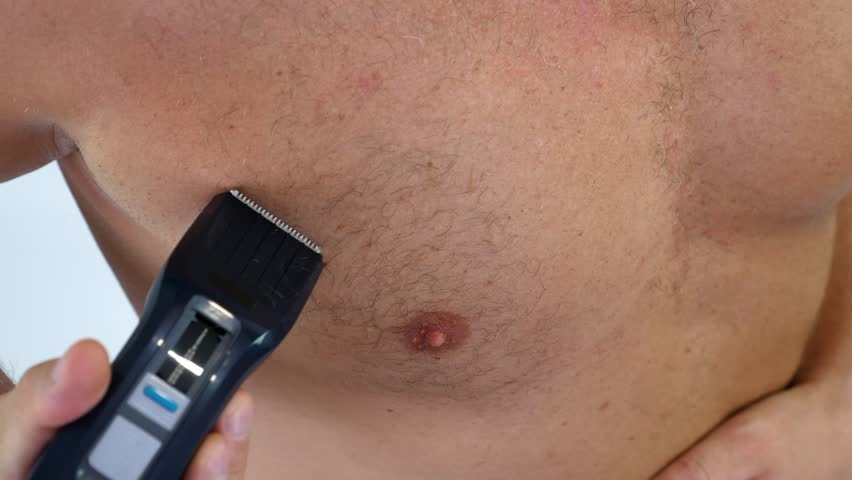 Close-up of a very hairy Man haircut body hair on his, male chest by himself with a clipper, electric razor, trimer. isolated on white background. Naked man shaves his chest