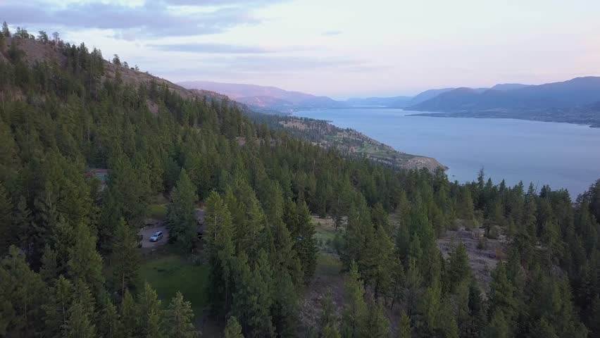Drone shot of Okanagan Lake and Valley. British Columbia at sunrise . Hills in morning light, distant vineyards. Some smoke from wildfires. Filmed in aerial drone view from above close over forest.