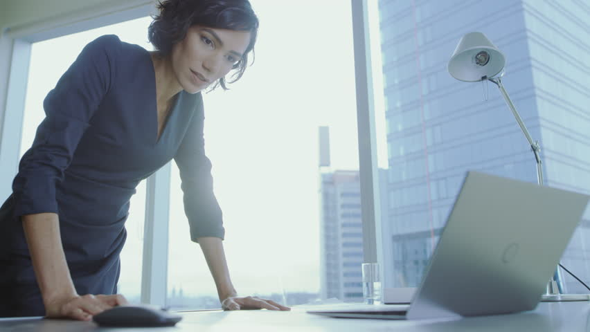 Low Angle Shot of Confident Businesswoman Leans on Her Office Desk, Writes Down Information in Documents and Looks at Laptop. Successful Woman Doing Business. Shot on RED EPIC-W 8K Helium Camera. Royalty-Free Stock Footage #1016145733