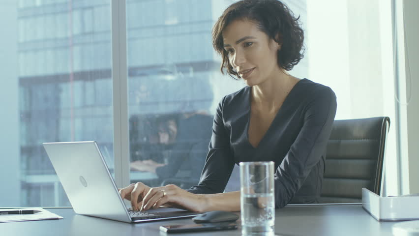 Confident Female Executive Works on a Laptop Sitting at Her Desk in Modern Office with Big City View. Smiling Successful Busiesswoman Uses Laptop. Shot on RED EPIC-W 8K Helium Cinema Camera.