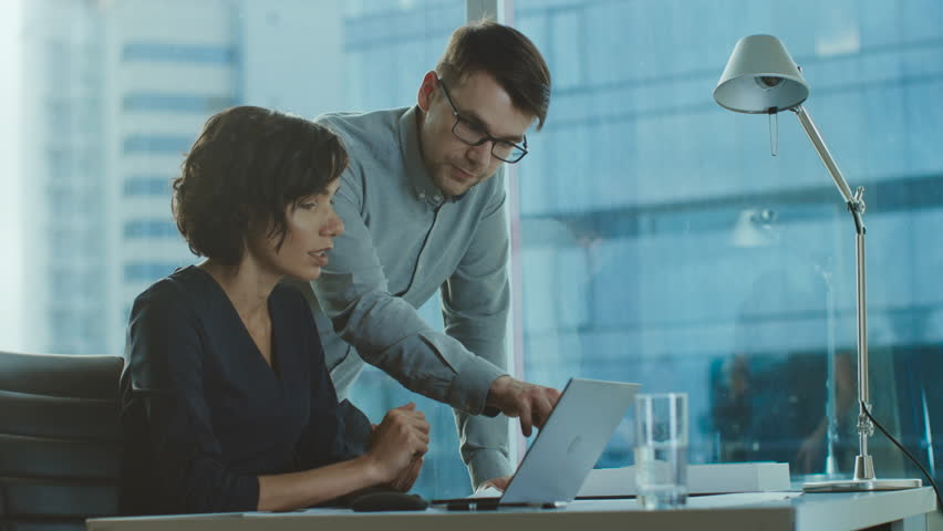 Beautiful Businesswoman Listens to Professional Advisor in Her Office, They Discuss Data Show on a Laptop. Smart Young Businesspeople Working in Finance. Shot on RED EPIC-W 8K Helium Cinema Camera. Royalty-Free Stock Footage #1016145916