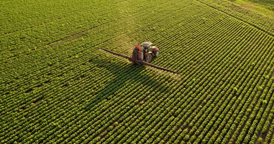 Aerial drone shot of a farmer spraying soybean fields #1016154847