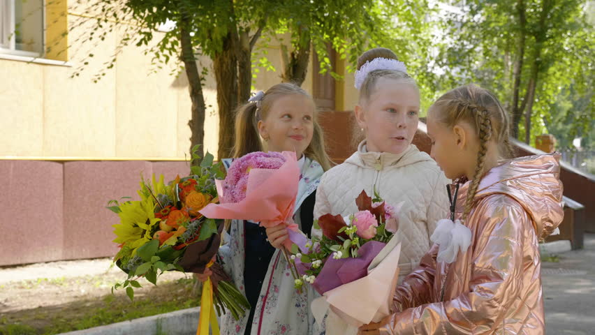 Cheerful schoolgirls with flowers talking and standing near school together