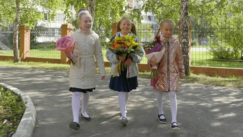 Three happy schoolgirls with flower bouquets going back to school