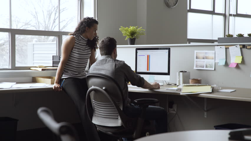 Dolly shot of business people discussing over desktop computer in office | Shutterstock HD Video #1016156401