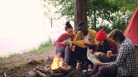 Cinemagraph loop - happy young people friends looking at maps sitting in forest around fire and holding drinks. Flame is moving, tent and trees are visible.
