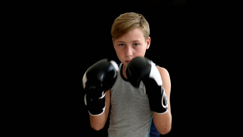 A teenage boxer with blond hair and dark eyes stands on a dark background. Hands of a teenager descend along the body, on it - a gray shirt without sleeves, a dark background. | Shutterstock HD Video #1016162647