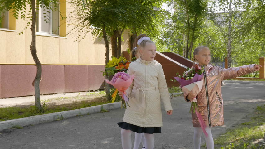 Three schoolgirls with bouquets pointing somewhere with fingers