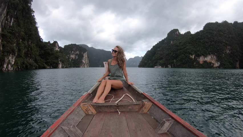 Beautiful girl traveling by boat in mountain tropical lake, the wind fluttering hair. Summer Travel concept, Thailand, Cheow lan lake | Shutterstock HD Video #1016166862