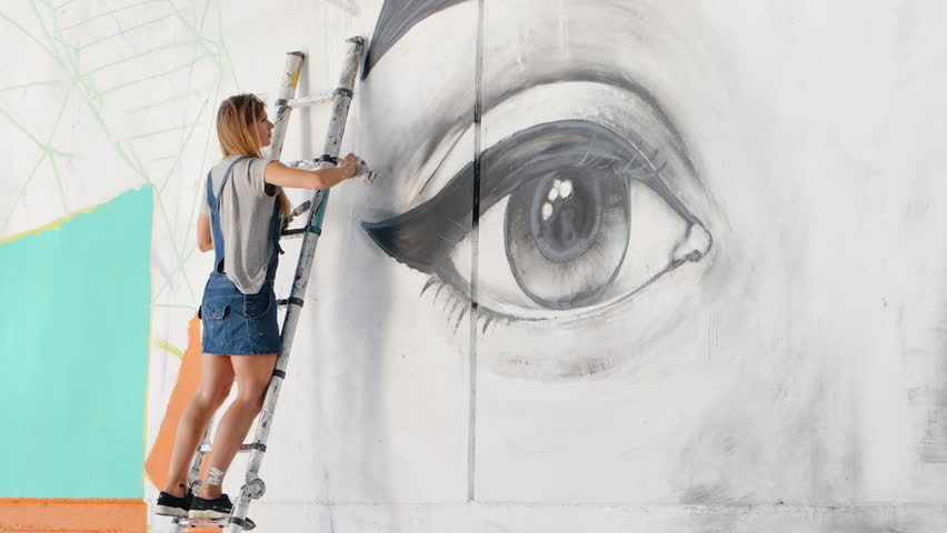 Beautiful girl making graffiti of big female face with aerosol spray on urban street wall. She standing on ladder. Creative art. Talented student in denim overalls drawing picture