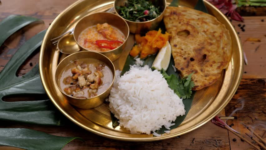 Assorted indian sri-lanka food set on wooden background. Dishes and appetisers of indeed cuisine, rice, lentils, paneer, samosa, spices, masala. Bowls and plates with indian food top view chicken Royalty-Free Stock Footage #1016176414