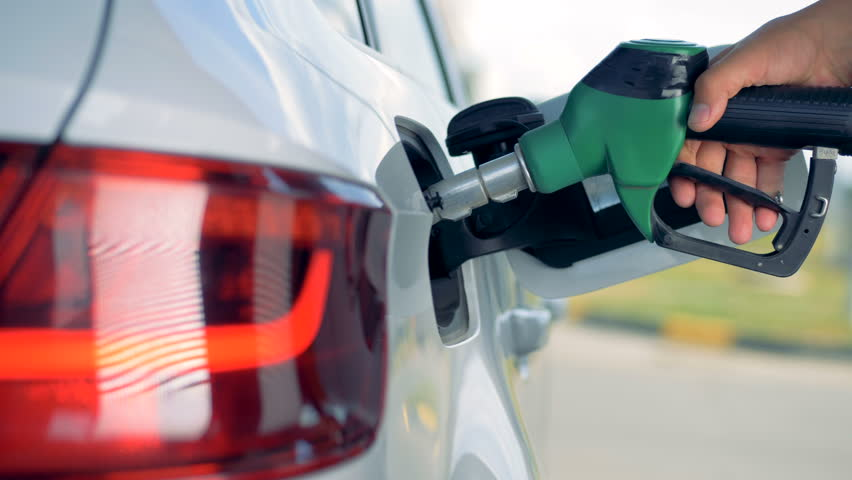 Fuel nozzle is getting inserted into automobile's tank. Fuel, gas station, petrol prices concept.