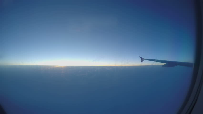 Passenger pov through plane window during flight. Aircraft flying above clouds #1016188888