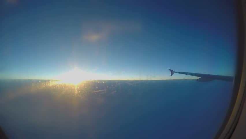 Beautiful sunrise in sky, plane wing seen through aircraft window, passenger pov #1016188891