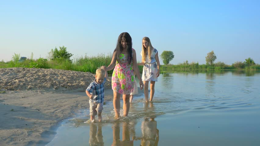 Two Young Beautiful Mothers Walk And Play In Water With Their Children. Summer River Morning Sunny Day Blue Sky. Slow motion 30p 0.5 60p