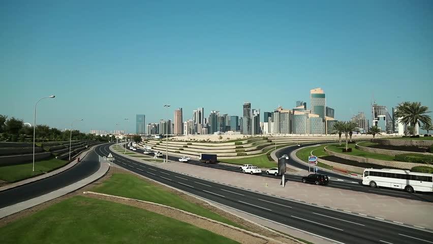 Road traffic near financial centre in Doha city, Qatar. View on Khalifa Partial Cloverleaf Interchange Park and skyscrapers in Doha downtown, Qatar, Persian Gulf, Arabian Peninsula, Middle East   Shutterstock HD Video #1016197024