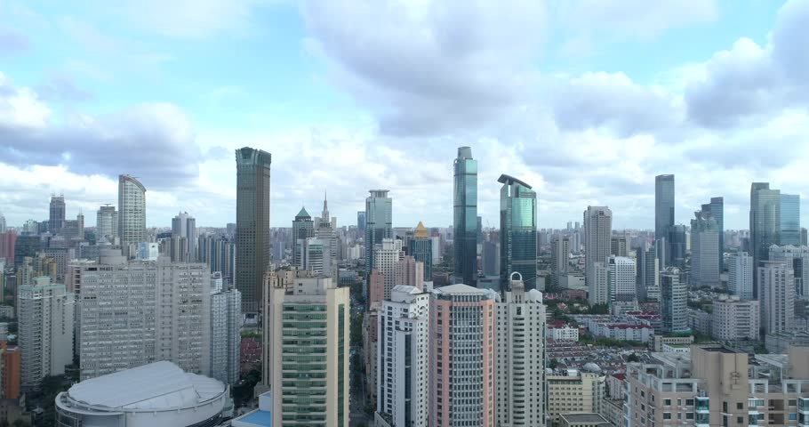 Ascending drone flight showing cityscape of modern megacity with highly populated build environment.  Jing'an District shown in the foreground is one of the central districts of Shanghai. Part 1 of 2. | Shutterstock HD Video #1016203771