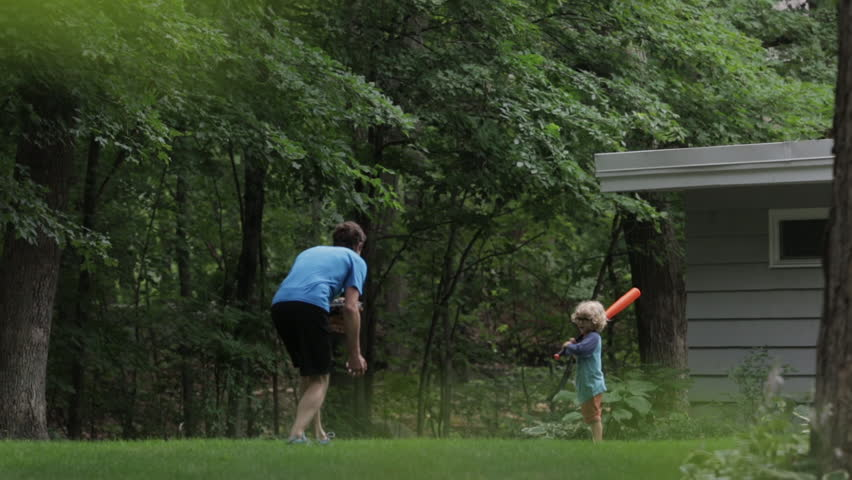 Cheerful boy playing baseball with father at yard #1016209147