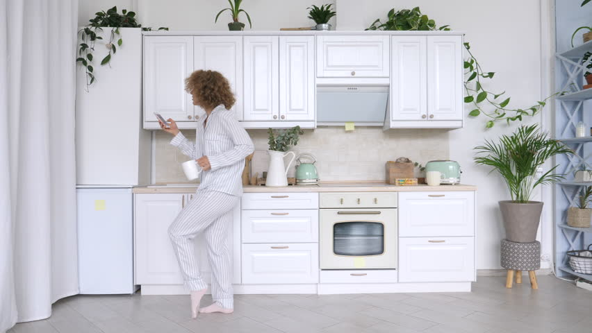 Young Woman Dancing And Using Cellphone In Kitchen. #1016210140