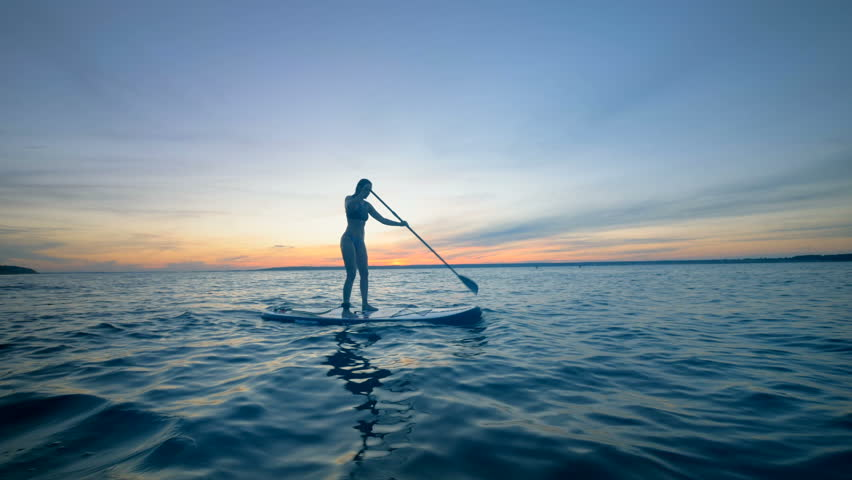 Young Attractive Woman woman is standing on a swimming board and paddling | Shutterstock HD Video #1016211652