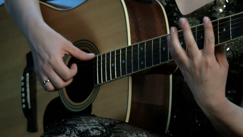 Close-up of the hands of a girl playing an acoustic guitar. Focus on the fingers clamping the chords on the fretboard. Day of music.