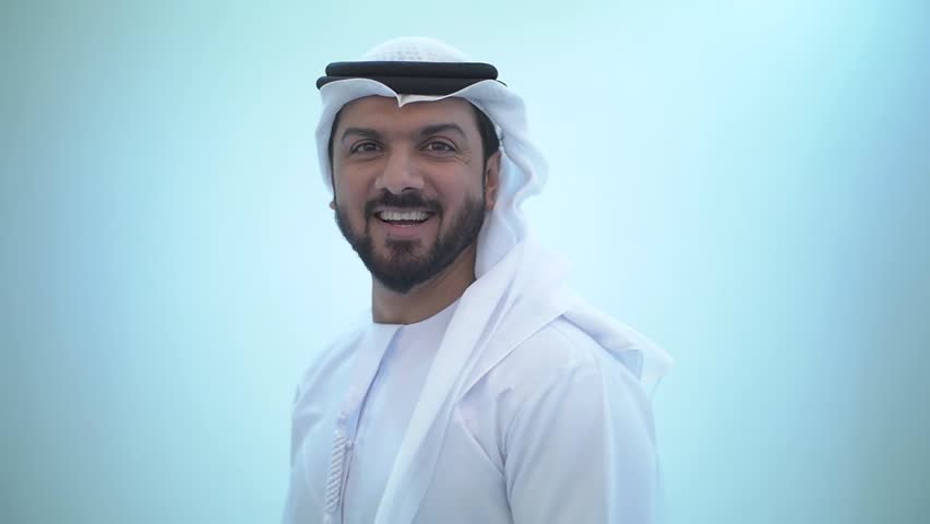 Smiling man wearing traditional emirates clothes, in dubai. studio footage with different poses