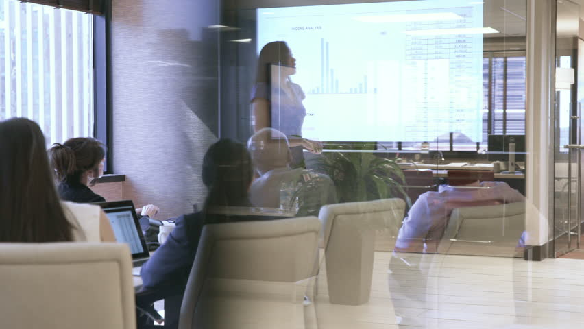 Dolly shot of businesswoman with colleagues analyzing data in board room