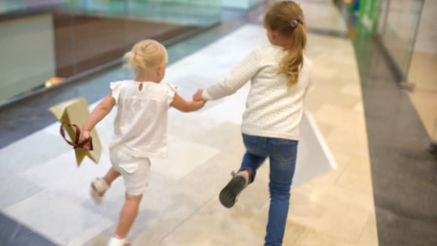 Shopping day of a happy family. little girls with packages walks with family on big shopping mall center. children running with bags on mall. shopping girl bag. happy family shopping child slow-motion #1016252878