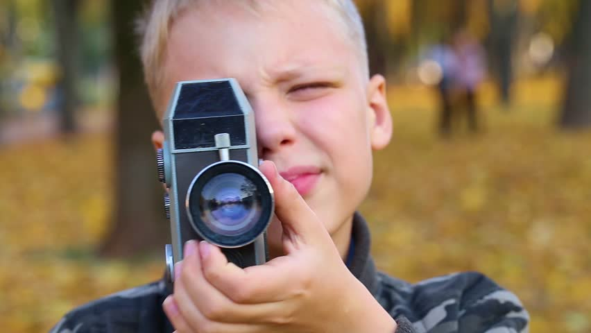 Closeup view of cute face of blond white kid holding vintage black camera for shooting video. Boy isolated on golden autumnal nature background. Real time full hd video footage. #1016254162