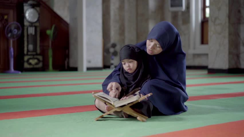 Asian Indonesian Muslim mother is teaching on how to read the quran to her daughter in the holy Mosque. Islam,religion and knowledge concept. Royalty-Free Stock Footage #1016267218