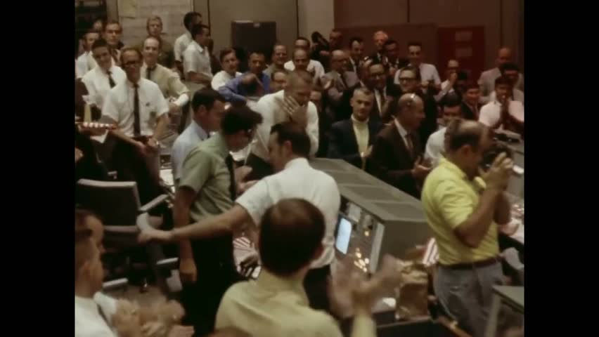CIRCA 1969 - NASA employees celebrate Apollo 11's victorious return; screens in the Mission Control Center show helicopters recovering the astronauts.