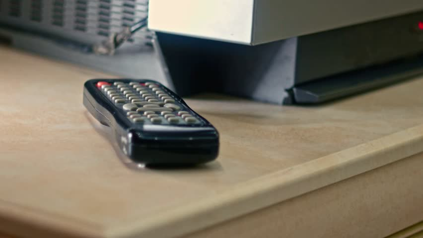 Male take remote TV control off the table near TV 4k Footage
