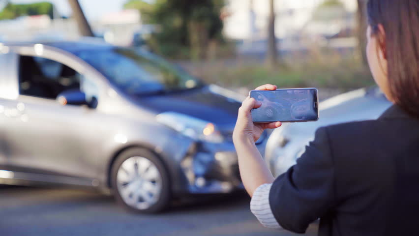 A female insurance agent taking photo of car accident on her smartphone. Two broken cars after car accident standing on the road. 4K UHD.