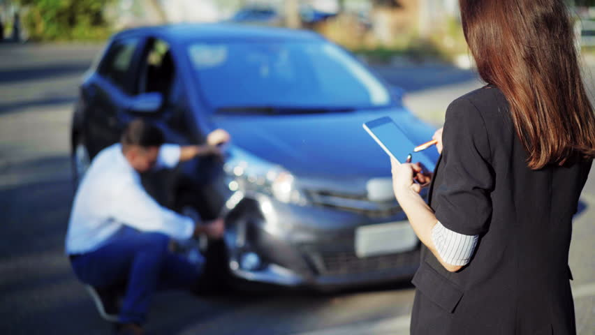 Insurance concept. Female insurance agent inspects damage to a man's car and makes notes on a tablet computer, during discussion with man. Woman with digital tablet inspecting broken car. 4K UHD.