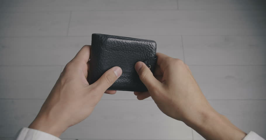 Close-up of a man's hand holding Leather Wallet Empty with No Money. The concept of poverty