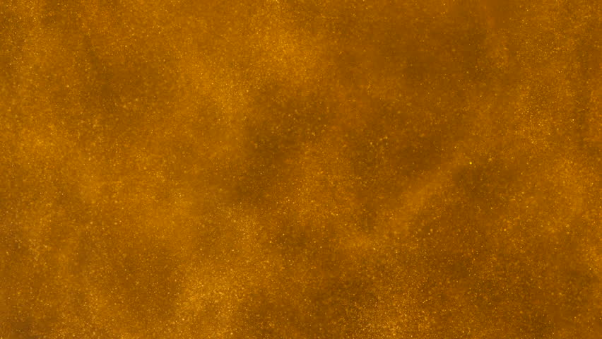 Gold ink in water shooting with high speed camera. Golden glitter sand or dust creating abstract cloud formations metamorphosis. Art backgrounds. Macro view.