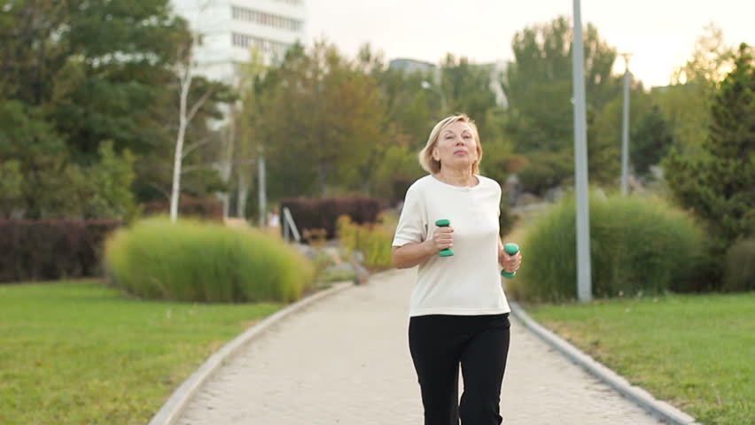 Elderly woman jogging with dumbbells in the park | Shutterstock HD Video #1016305582